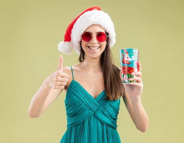 Улыбающаяся молодая кавказская девушка в солнцезащитных очках в шляпе санта-клауса держит бумажный стаканчик и показывает палец вверх