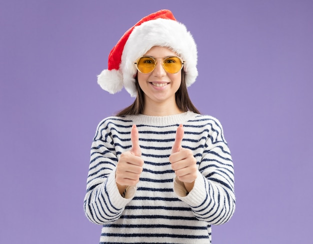 산타 모자 엄지 손가락으로 태양 안경에 웃는 젊은 백인 여자