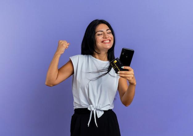 La giovane ragazza caucasica sorridente tiene il pugno e tiene la carta di credito del telefono