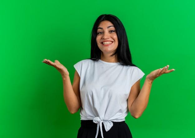 La giovane ragazza caucasica sorridente tiene le mani aperte