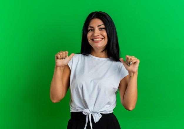 La giovane ragazza caucasica sorridente indica se stessa con due mani