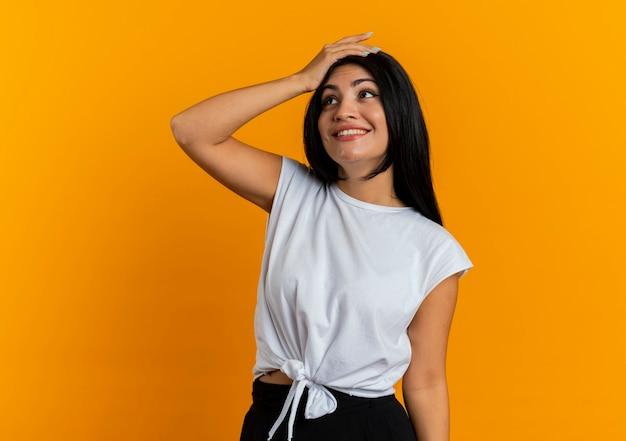 La giovane ragazza caucasica sorridente mette la mano sulla testa che esamina il lato