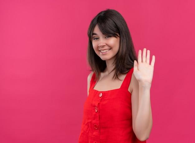 笑顔の若い白人の女の子が手を上げて、コピースペースで孤立したピンクの背景にカメラを見て