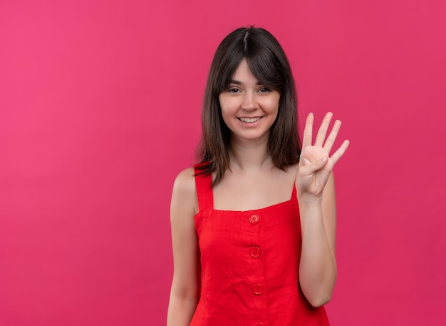 Улыбающаяся молодая кавказская девушка показывает четыре пальцами на изолированном розовом фоне с копией пространства