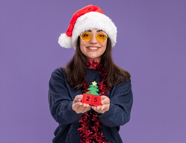 Smiling young caucasian girl in sun glasses with santa hat and garland around neck holding christmas tree ornament isolated on purple wall with copy space