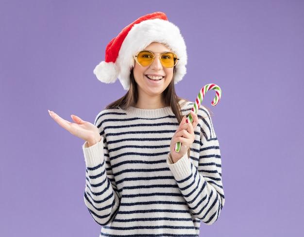 Sorridente giovane ragazza caucasica in occhiali da sole con cappello da babbo natale che tiene un bastoncino di zucchero isolato sulla parete viola con spazio di copia