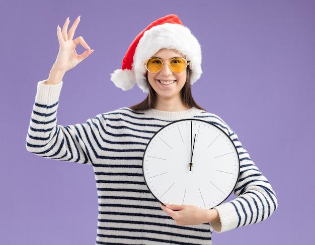 Sorridente giovane ragazza caucasica in occhiali da sole con cappello santa tenendo l'orologio e gesticolando segno ok