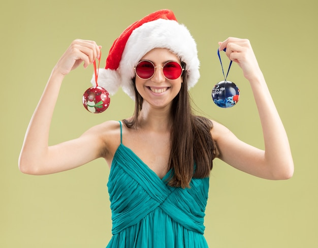 Smiling young caucasian girl in sun glasses with santa hat holding glass ball ornaments isolated on olive green wall with copy space