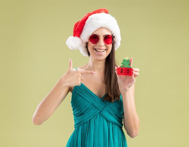 Sorridente giovane ragazza caucasica in occhiali da sole con cappello santa tenendo e indicando l'ornamento dell'albero di natale