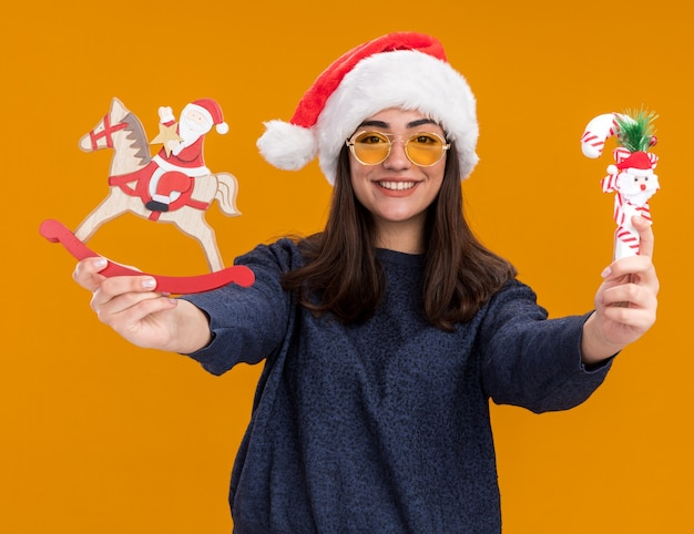 Smiling young caucasian girl in sun glasses with santa hat holding santa on rocking horse decoration and candy cane isolated on orange wall with copy space