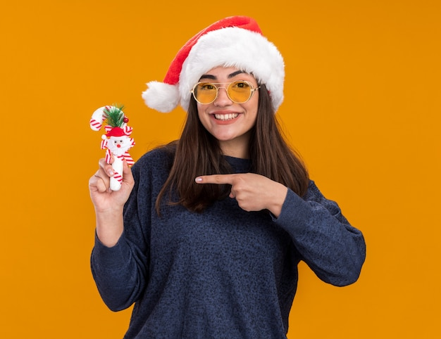 Smiling young caucasian girl in sun glasses with santa hat holds and points at candy cane isolated on orange wall with copy space