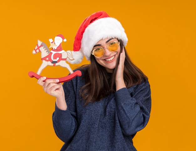Smiling young caucasian girl in sun glasses with santa hat puts hand on face and holds santa on rocking horse decoration isolated on orange wall with copy space