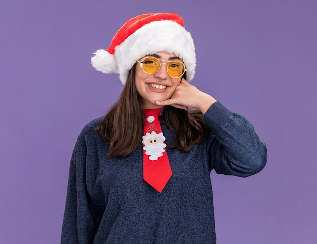 Smiling young caucasian girl in sun glasses with santa hat and santa tie gesturing call me sign isolated on purple background with copy space