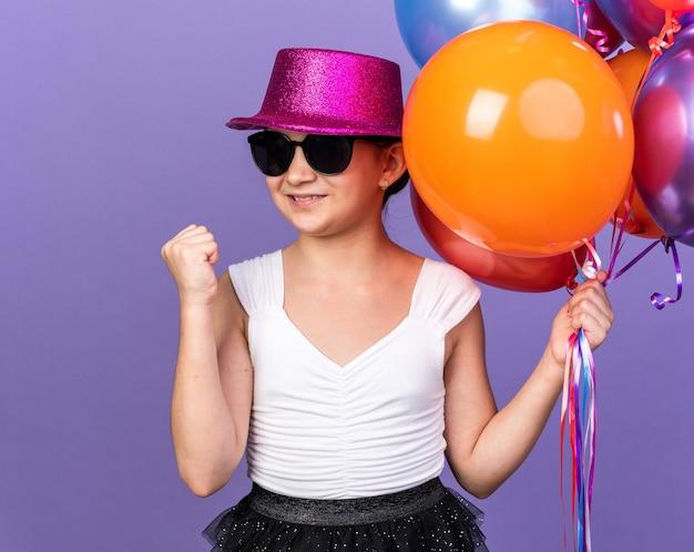 Sorridente giovane ragazza caucasica in occhiali da sole con cappello da festa viola che tiene palloncini di elio e tiene il pugno alzato isolato sulla parete viola con spazio di copia