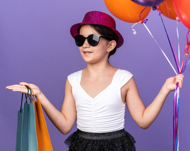 Smiling young caucasian girl in sun glasses with violet party hat holding helium balloons and shopping bags looking at side isolated on purple wall with copy space