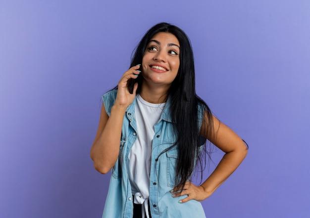 전화에 웃는 젊은 백인 여자 회담 측면을보고 허리에 손을 넣습니다