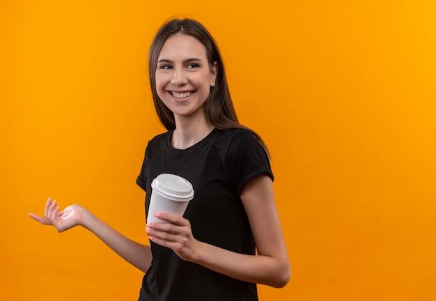 격리 된 오렌지 배경에 커피 한잔 들고 측면에서 찾고 검은 티셔츠를 입고 웃는 젊은 백인 여자