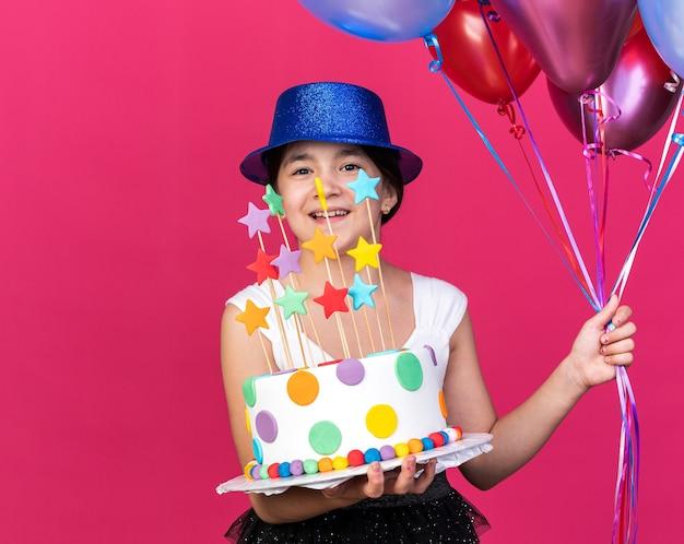 Улыбающаяся молодая кавказская девушка в синей партийной шляпе держит праздничный торт и гелиевые шары, изолированные на розовой стене с копией пространства