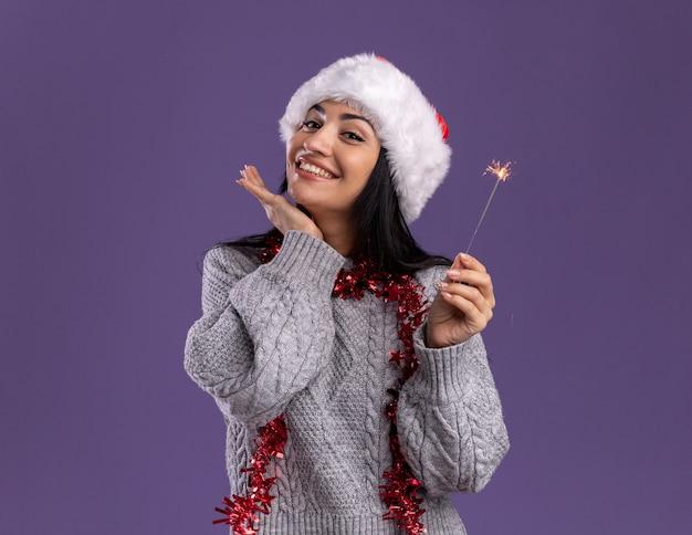 Улыбающаяся молодая кавказская девушка в рождественской шапке и гирлянде из мишуры на шее держит праздничный бенгальский огонь, глядя в камеру, держа руку под подбородком, изолированную на фиолетовом фоне с копией пространства
