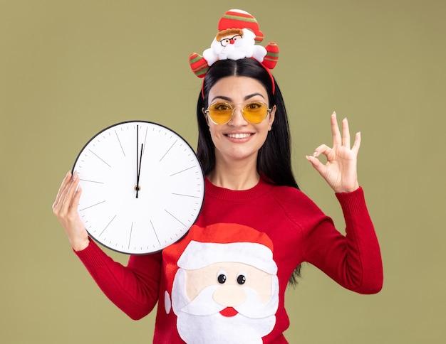 サンタクロースのヘッドバンドとセーターを着て、時計を持って、オリーブグリーンの背景に分離されたokサインをしているカメラを見て笑顔の若い白人の女の子