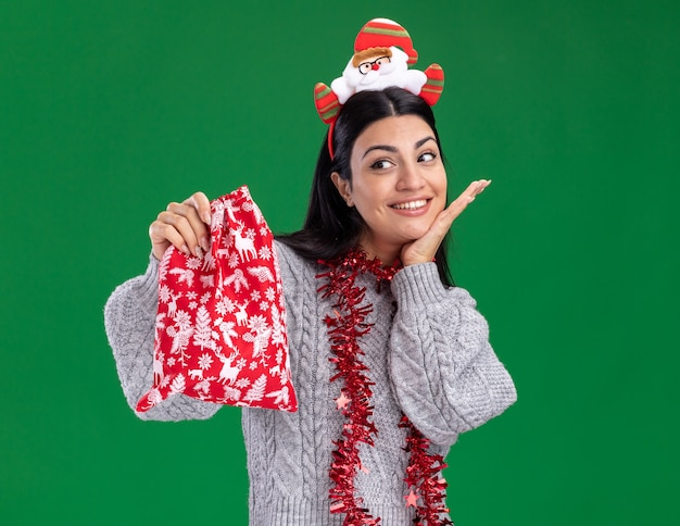 サンタ クロースのカチューシャと見掛け倒しの花輪を首に身に着けている笑顔の若い白人の女の子がクリスマス プレゼントの袋を持って、コピー スペースで緑の壁に隔離されたあごの下に手を保つ側を見て