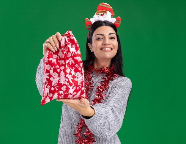 サンタ クロースのカチューシャと見掛け倒しの花輪を身に着けている笑顔の若い白人の女の子は、コピー スペースを持つ緑の壁に向かってクリスマス プレゼントの袋を伸ばして首の周り