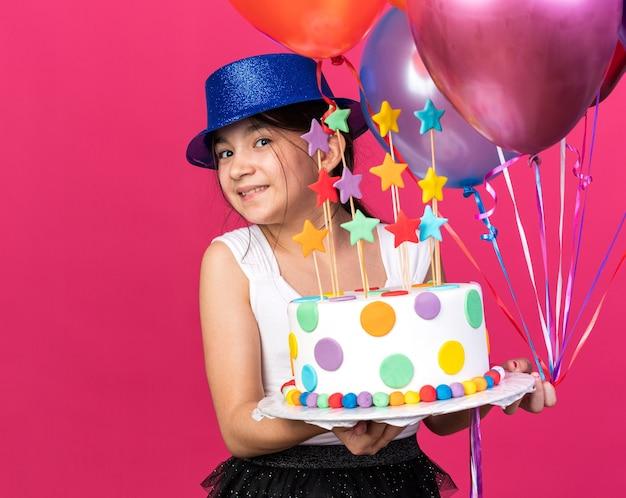 Sorridente giovane ragazza caucasica con blue party hat tenendo la torta di compleanno e palloncini di elio isolati sulla parete rosa con spazio di copia