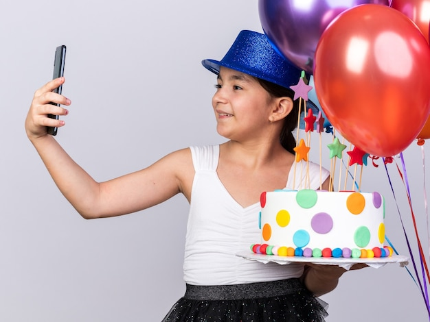 Smiling young caucasian girl with blue party hat holding helium balloons and birthday cake taking selfie on phone isolated on white wall with copy space