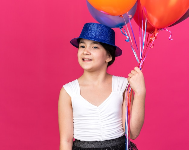 Smiling young caucasian girl with blue party hat holding helium balloons isolated on pink wall with copy space