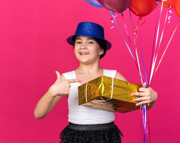 Smiling young caucasian girl with blue party hat pointing at gift box and holding helium balloons isolated on pink wall with copy space