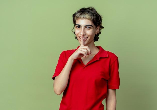 コピースペースとオリーブグリーンの背景に分離されたピクシーヘアカットジェスチャー沈黙と笑顔の若い白人の女の子