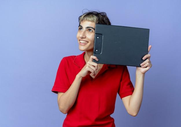 それで顔に触れるクリップボードを保持し、コピースペースで紫色の背景に孤立して見上げるピクシーヘアカットで若い白人の女の子を笑顔