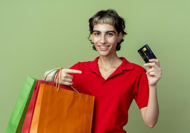 Sorridente giovane ragazza caucasica con taglio di capelli pixie che tiene borse della spesa e carta di credito che punta alla carta su spazio verde oliva