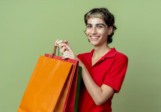 オリーブグリーンの背景で隔離の買い物袋を保持しているピクシーヘアカットと笑顔の若い白人の女の子