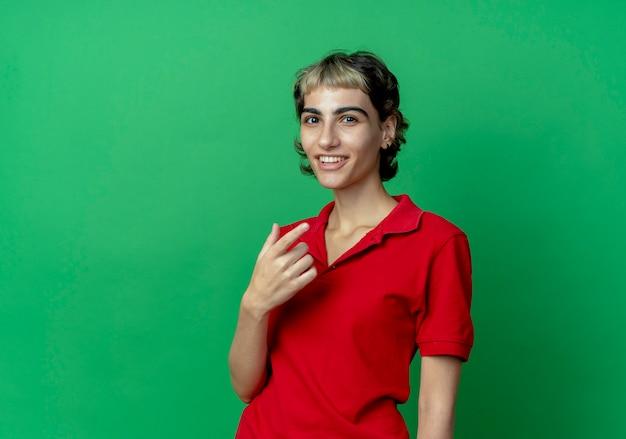 복사 공간 녹색 배경에 고립 된 공기에 손을 유지 픽시 머리와 젊은 백인 여자 미소