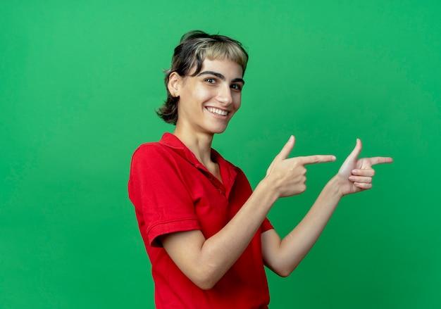 복사 공간 녹색 배경에 고립 된 측면에서 가리키는 요정 머리와 웃는 젊은 백인 여자