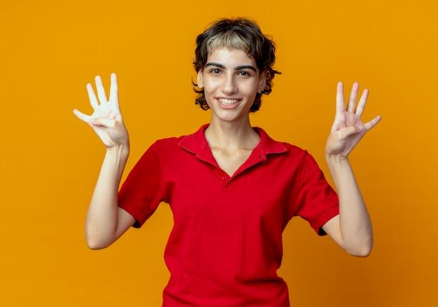 オレンジ色の背景に分離された手で8を示すピクシーヘアカットと笑顔の若い白人の女の子