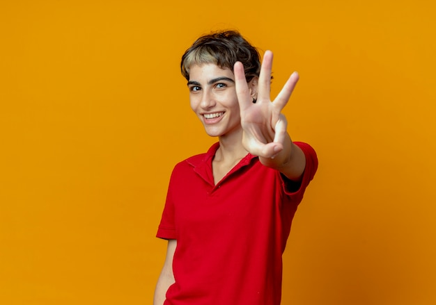 Smiling young caucasian girl with pixie haircut showing three at camera isolated on orange background with copy space