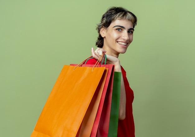 Улыбающаяся молодая кавказская девушка со стрижкой пикси, стоящая в профиль, держит сумки на плече, изолированные на оливково-зеленом фоне с копией пространства