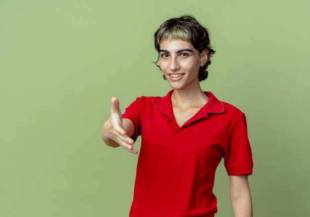Smiling young caucasian girl with pixie haircut stretching out hand gesturing hi isolated on olive green background with copy space