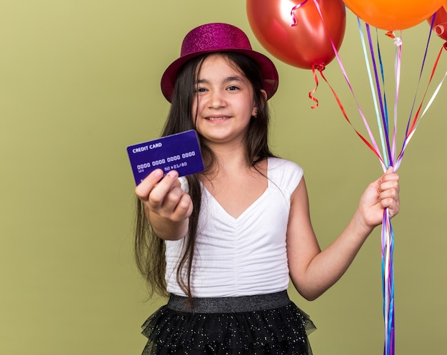 Smiling young caucasian girl with purple party hat holding credit card and helium balloons isolated on olive green wall with copy space
