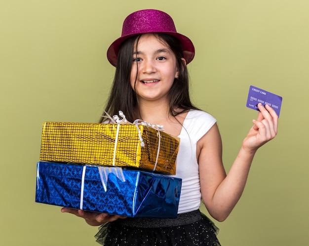 Улыбающаяся молодая кавказская девушка в фиолетовой партийной шляпе держит подарочные коробки и кредитную карту, изолированную на оливково-зеленой стене с копией пространства