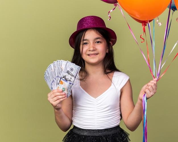 Улыбающаяся молодая кавказская девушка в фиолетовой партийной шляпе держит деньги и гелиевые шары, изолированные на оливково-зеленой стене с копией пространства