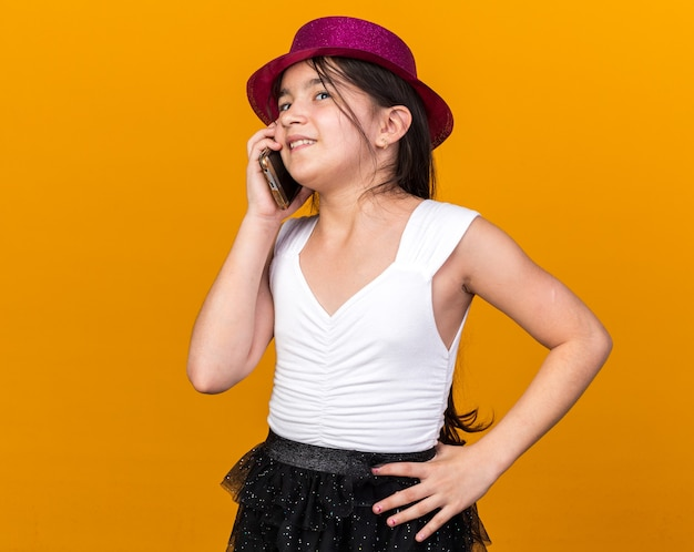 Улыбающаяся молодая кавказская девушка с фиолетовой партийной шляпой разговаривает по телефону на оранжевой стене с копией пространства