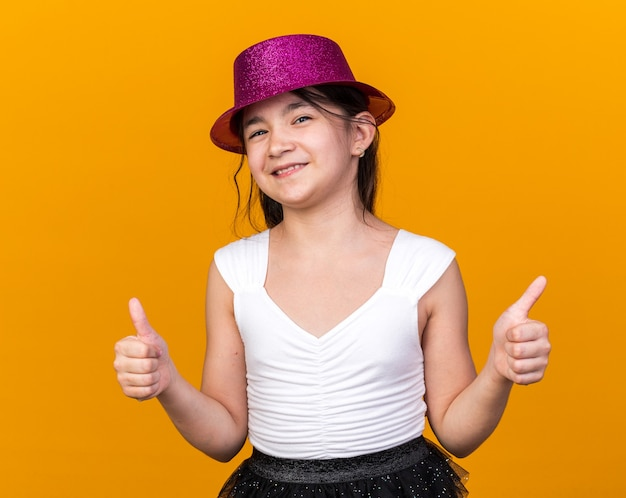 Smiling young caucasian girl with purple party hat thumbing up isolated on orange wall with copy space