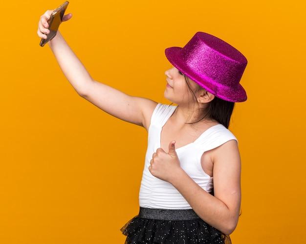 Улыбающаяся молодая кавказская девушка с фиолетовой партийной шляпой показывает палец вверх, принимая селфи на телефоне, изолированном на оранжевой стене с копией пространства