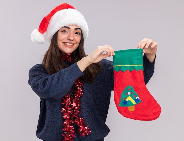 Улыбающаяся молодая кавказская девушка в новогодней шапке и гирлянде на шее держит рождественский чулок на белом фоне с копией пространства