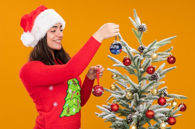 Улыбающаяся молодая кавказская девушка в новогодней шапке украшает елку стеклянными шарами, изолированными на оранжевом фоне с копией пространства