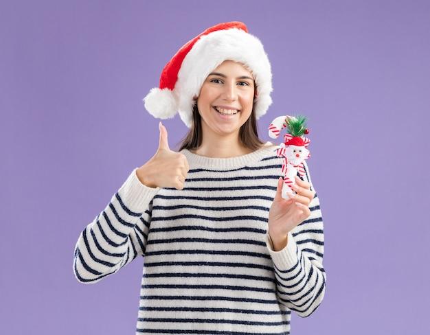 La giovane ragazza caucasica sorridente con il cappello della santa tiene il bastoncino di zucchero ed i pollici in su
