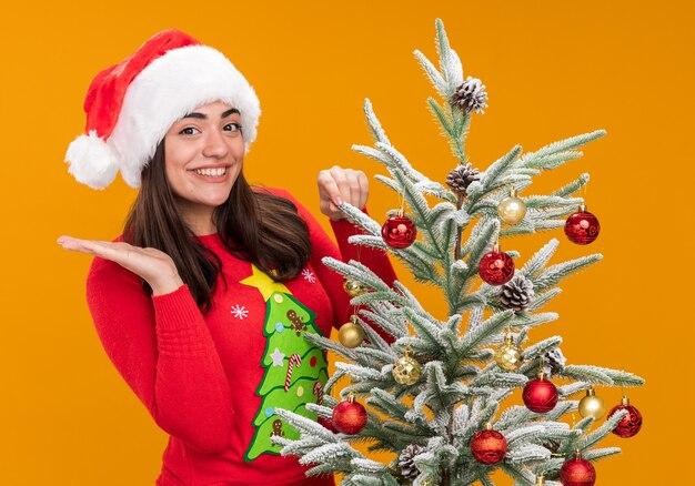 Sorridente giovane ragazza caucasica con santa cappello tiene la mano aperta in piedi dietro l'albero di natale isolato su sfondo arancione con spazio di copia